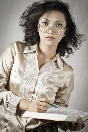 Portrait asia girl with curly hair wearing a formal shirt with old glasses in the studio  photo