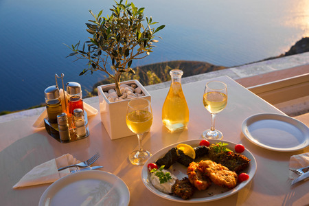 Romantic dinner for two at sunset.Greece, Santorini, restaurant on the beach, above the volcano. The view from the top. Stock Photo - 58798816
