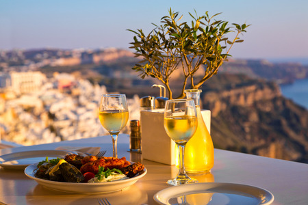 Dinner for two at sunset.Greece, Santorini, restaurant on the beach, above the volcano Stock Photo - 58799194