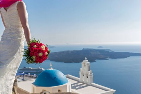 love dome: Bride with a bouquet of flowers in his hands stands high over the coast. Santorini, Greece. Stock Photo