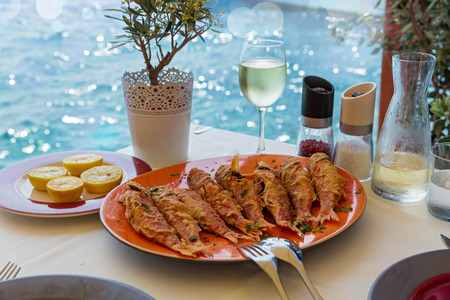 mullet: Fried red mullet fish on the plate, restaurant on the beach Stock Photo