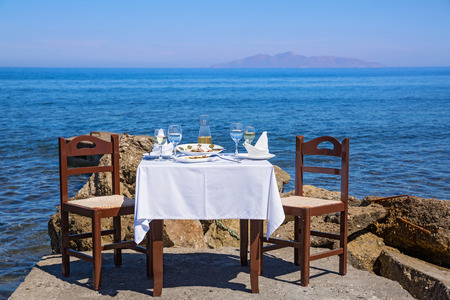 turquoise water: Table for lunch at Navy pier, Greece, Santorini Stock Photo