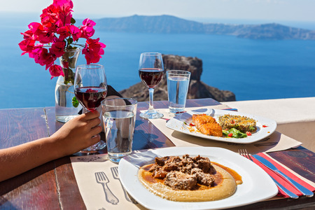 Meal for two at a street restaurant in Santorini, overlooking the volcano Stock Photo - 66801970