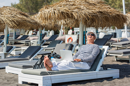 he laughs: Man laughs, he is resting on the beach and working remotely