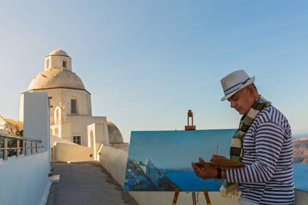 Man with the easel the sea draws and a Church Greece, Santorini