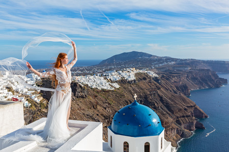 Beautiful young woman in white dress stands on the roof and looks at the island of Santorini, Greece
