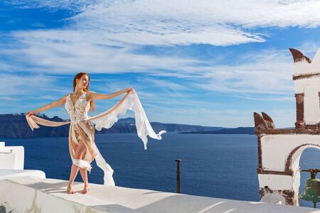 Beautiful young woman in white dress stands on the roof near the bells on Santorini island, Greece