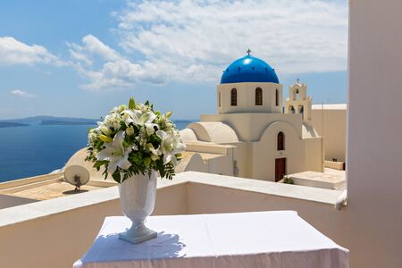 vasi greci: Wedding bouquet in a white vase on a background of the dome Church in Santorini