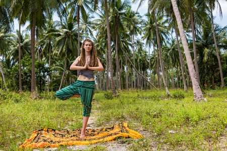 Young woman with dreads does yoga surrounded by palm trees
