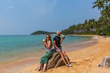 Young couple drinking fresh coconut juice on the beach