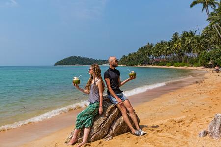 rastas: Pareja joven bebiendo jugo de coco fresco en la playa