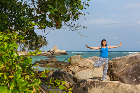 Woman on the seafront, is engaged in sports and yoga.