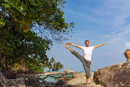 Man on the beach, is engaged in sports and yoga.