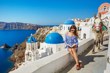 Young woman in a blue dress reading a book, Greece, Santorini
