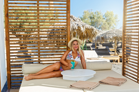 Beautiful woman in a swimsuit sunbathing on the beach couch under a canopy.