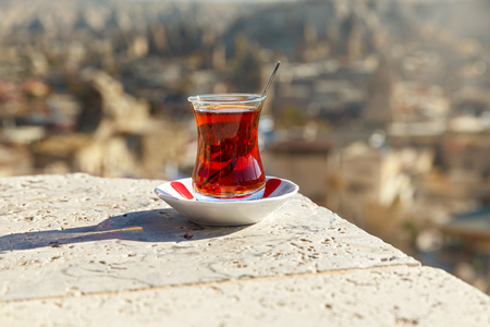 Hot tea in a transparent glass on the background of the city of Turkey