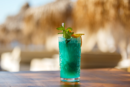 Crystal glass of green drink on the beach table Stock Photo - 115812987