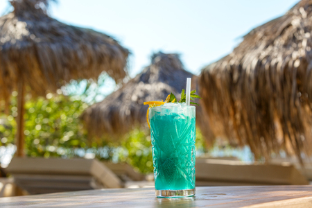 Crystal glass of green drink on the beach table