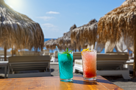 Two glasses with a refreshing drink on the table on the background of the beach and the sea Stock Photo