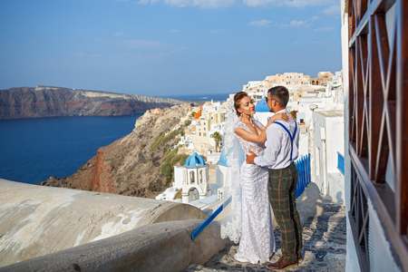 Beautiful wedding couple on a background of white architecture on Santorini island, Greece
