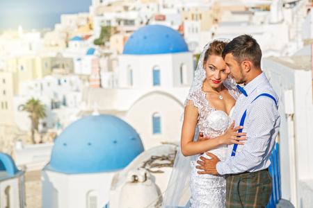 Beautiful wedding couple on a background of white architecture on Santorini island, Greece