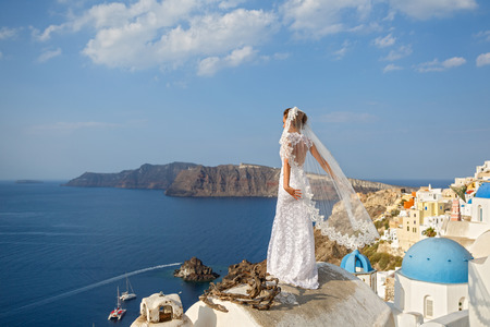Bride in white dress on the high roof of Santorini, over the sea Stock Photo - 115813050