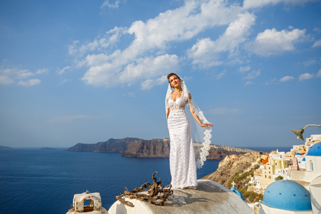 Bride in white dress on the high roof of Santorini, over the sea