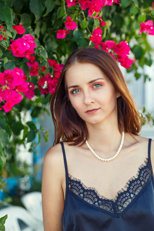 Portrait of a young beautiful woman on the background of flowering bushes Stock Photo