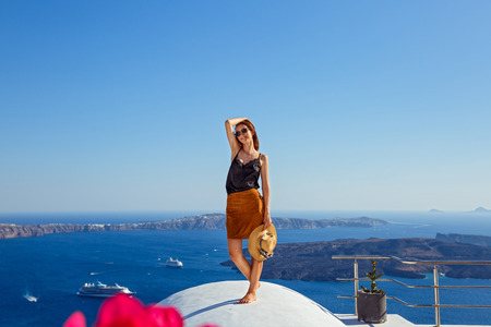 Young woman on white roof of a building in Santorini, over the sea