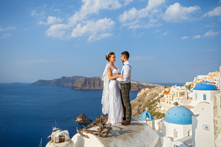 Bellissimi sposi su uno sfondo di architettura bianca e mare sull'isola di Santorini, Grecia