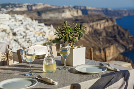 Table with a bottle of wine and glasses on the background of Santorini, Greece
