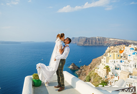 Beautiful wedding couple on a background of white architecture and sea on Santorini island, Greece Stock Photo