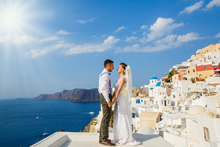 Beau couple de mariage à Santorin, en Grèce. Tenir les mains contre la mer Banque d'images