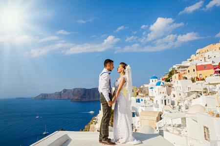 Hermosos novios en Santorini, Grecia. Tomate de la mano contra el mar Foto de archivo