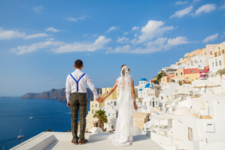 Beautiful wedding couple in Santorini, Greece. Look at the sea, the view from the back
