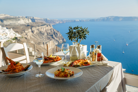 Dinner for two with fish dishes and white wine, a table on the background of the sea Stock Photo