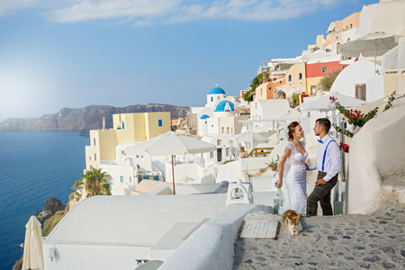 Beautiful wedding couple and red cat, on the background of the architecture of Santorini