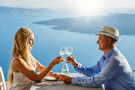 Adult couple having dinner and drinking wine in a restaurant on the background of the sea