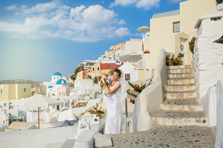 Beautiful woman in bride dress and red cat, on the background of the architecture of Santorini