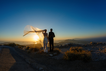 Silhouette of bride and groom on a high rock on a background of sea sunset