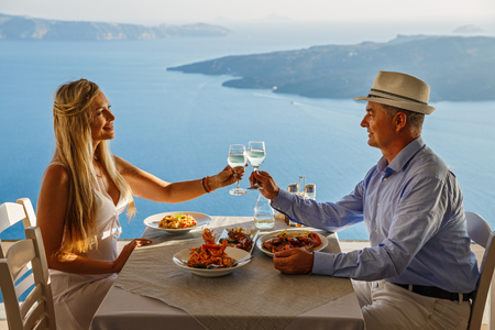 Man and woman having dinner in a restaurant on the background of the sea, Santorini island, Greece Stock Photo