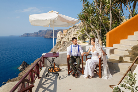 The bride and groom sitting at the table against the sea, Santorini island