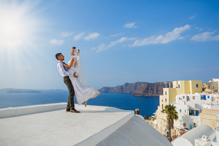 Beautiful wedding couple on the background of the sea and the island of Santorini