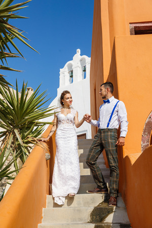 Groom gives his hand to the bride on the stairs, Greece, Santorini island