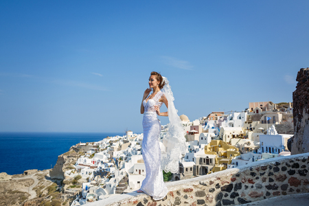 Beautiful bride stands at a high level above the sea on the background of architecture of Santorini, Greece Stock Photo