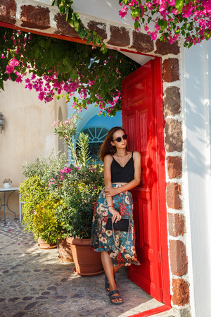 Young beautiful woman standing at the entrance of the house, Greece Stock Photo