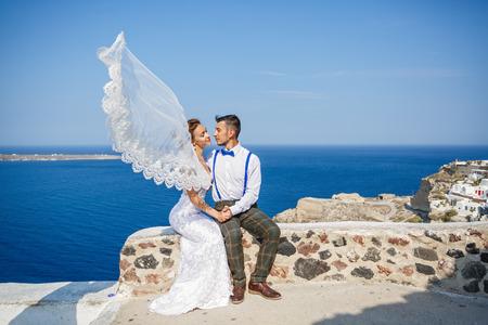 Groom kisses the bride, veil flutters in the wind. Greece, Santorini island Stock Photo