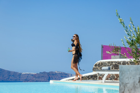 Young, beautiful woman standing on the edge of the pool with a drink in her hand and looking at the sea.