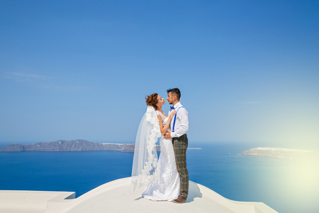 Beautiful couple standing on the roof high above the sea on the background of sky and sea in Santorini, Greece
