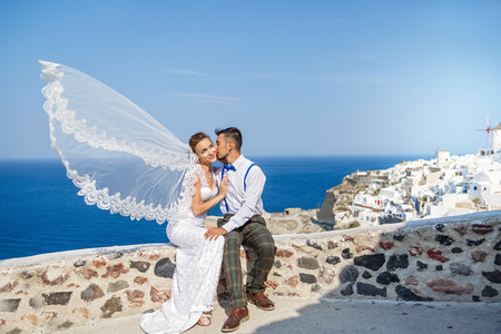 Groom kisses the bride, veil flutters in the wind. Greece, Santorini island 写真素材